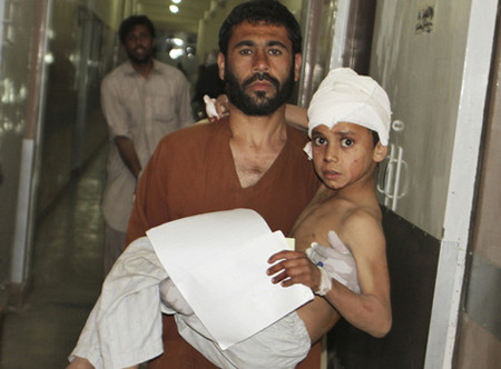 A young injured Afghan boy is carried by his father into the emergency room at the hospital in Kandahar