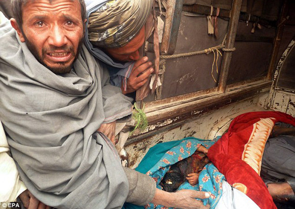 Two grief-stricken Afghan men look into the van where the body of a badly burned child lays, wrapped in a blue blanket