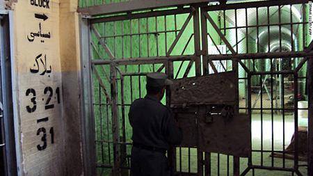 An Afghan policeman stands guard inside Kandahar jail
