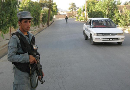 An Afghan policeman stands guard at the attack site in Kandahar province, southern Afghanistan, May 7, 2011.