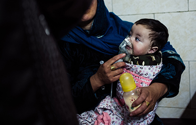 Khalid, 9 months old, is held by his mother as he receives treatment for a respiratory infection at the hospital in Kabul