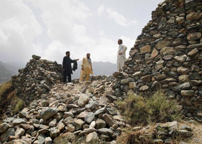 AP Afghan villagers in eastern Kunar province stand near the wall of a residential compound hit by a Pak artillery shell