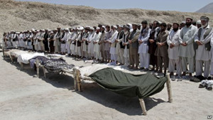 Afghan men offer funeral prayers near the bodies of 7 civilians killed