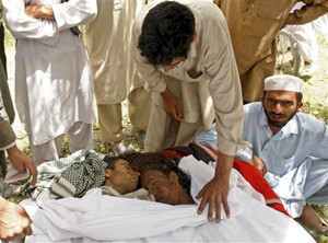 Men inspect the bodies of victims at the site of an explosion in Afghanistan's Logar province