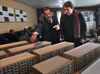 Mahmoud Karzai, right, brother of Afghan President Hamid Karzai, looks over a model of an apartment complex he and a partner are constructing in Kabul