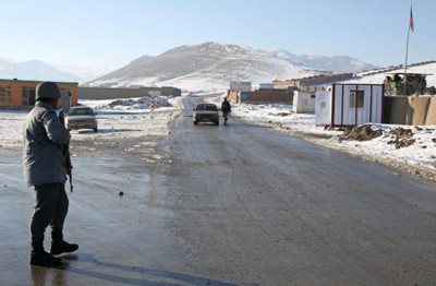 Afghan policemen stand guard at a check post in Kabul-Bamiyan road