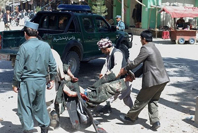 Afghan men carry a victim of a suicide attack in Maymana city of Faryab province