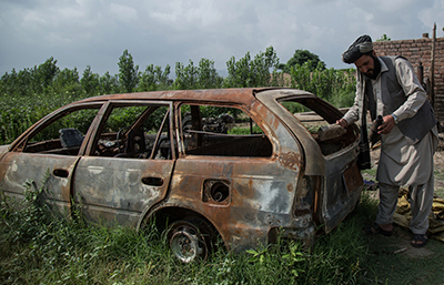 Noor Walli Khan stands near his burned-out car
