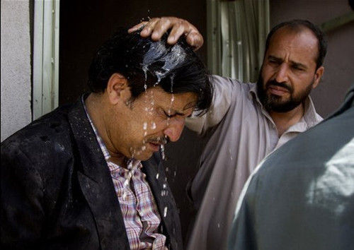 An Afghan man pours water over the head of his friend, left, who claims he has lost all his children at the scene where a suicide car bomber attacked a NATO convoy in Kabul