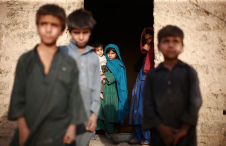 The children of a preacher from Kandahar stand around their mud-brick dwelling