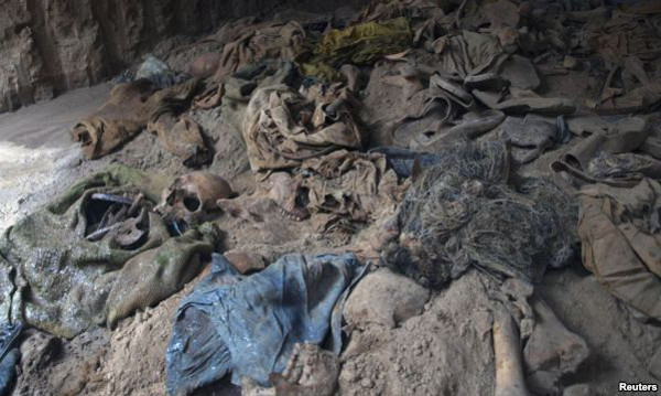 Human skeletons and items of clothing are seen in a mass grave uncovered in northern Balkh Province
