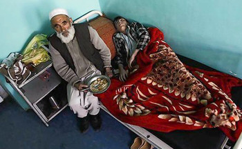 A man eats his lunch next to his son who is suffering from mental illness at a mental hospital in Kabul