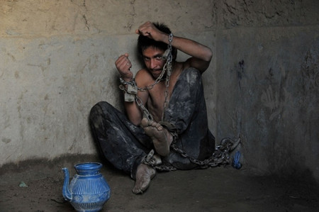 A mentally ill Afghan patient sits chained to a wall at the Mia Ali Baba holy shrine in the village of Samar Khel on the outskirts of Jalalabad