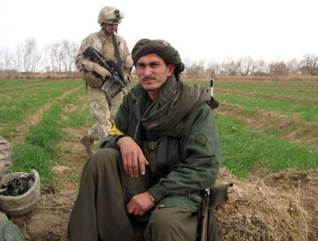 A member of new Afghan community militia rests during a patrol with U.S. Marines in Marjah, Afghanistan