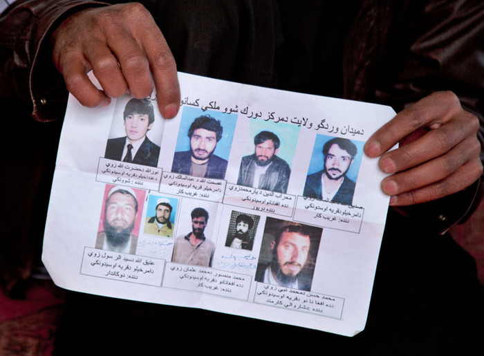 A missing-persons poster, with pictures of nine men who their relatives say were last seen being arrested by U.S. special operation forces, is held by a villager in Maidan Shahr, Afghanistan