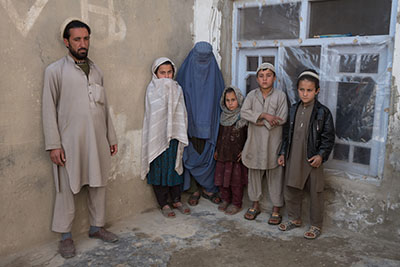 Mohammad, 30, and his family, in the courtyard of their home in Behsud District