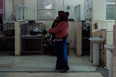 A mother carries her sick child inside the respiratory wing of the Indira Gandhi Children's Hospital in Kabul