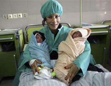 An Afghan woman holds her newborn twins at the Razai Foundation Maternity Hospital in Herat province