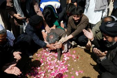 Afghan Shia Muslim men mourn over the grave of a victim who was killed in an attack at the Sakhi Shrine in Kabul, Afghanistan