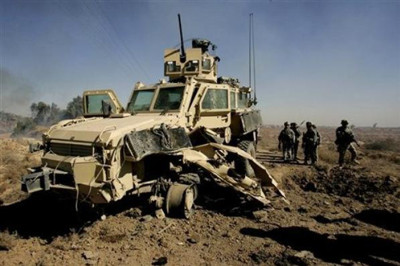 U.S. soldiers secure the area next to a damaged U.S. mine resistant, ambush protected vehicle (MRAP), after a roadside bomb explosion during an operation