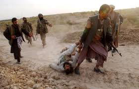 Northern Alliance's armed group torturing an injured Taliban prisoner