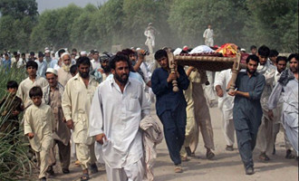 Afghan men shout anti-U.S. slogans as they carry the bodies of two people killed in a night raid in the eastern city of Jalalabad