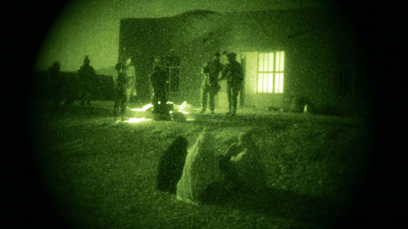 Afghan women and their children wait as U.S. Special Operations forces and Afghan National Army soldiers search their home during a joint operation