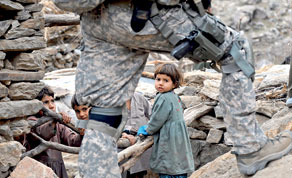 Afghan children watching a US soldier from the Provincial Reconstruction team (PRT)
