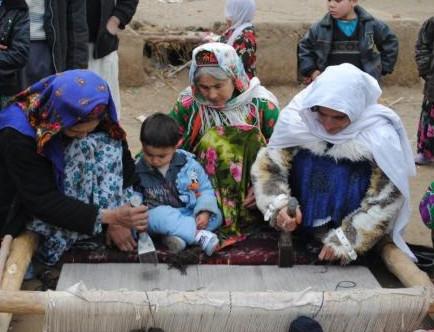 Several people work on a rug loom in Afghanistan
