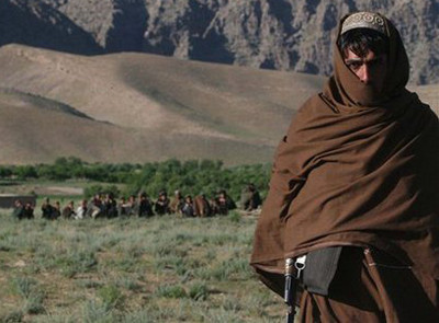 An Afghan militia guard as he looks on in a village Chenar Tu in Oruzgan