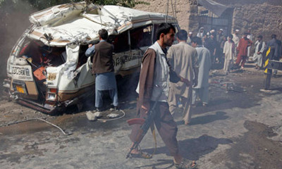 Afghan villagers stand next to the bus that was hit by a remote-controlled bomb in Kabul Afghanistan
