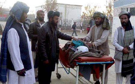Relatives move an injured victim of a landmine blast that killed seven children