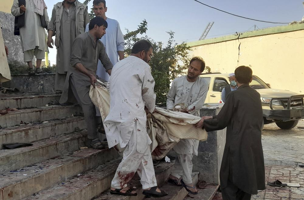 People carry the body of a victim from a mosque following a bombing