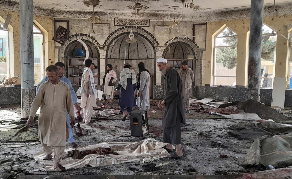 People view the damage inside of a mosque following a bombing