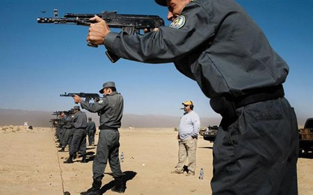 Afghani police use a rifle training course in Kabul as a DynCorp employee looks on