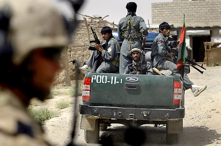 Afghan police officers sit in the back of a police truck, as a U.S. Marine is seen in the foreground in Aynak