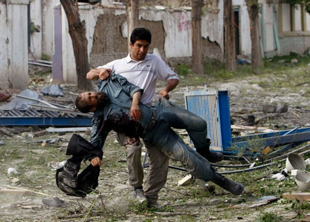 A wounded Afghan police officer was carried away from the scene