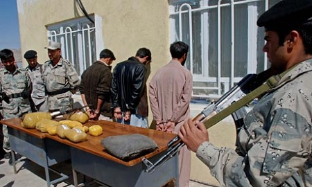 Afghanistan police guard three drug smugglers who were arrested with 87kg of opium in Herat city