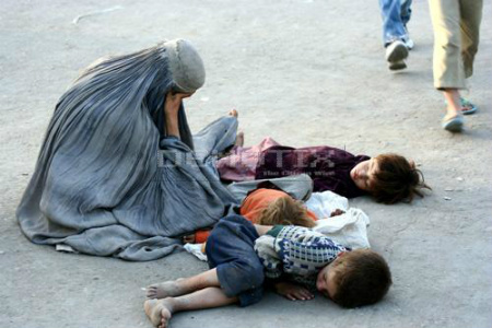 Afghan woman begging with her children
