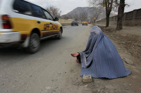 An Afghan woman begs along a busy Kabul street in February 2009