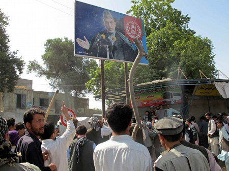 Afghans throw rocks at a picture of Afghanistan's President Hamid Karzai during a protest in Taloqan May 18, 2011
