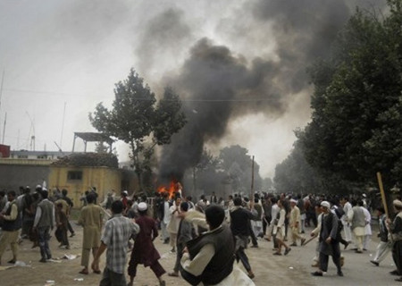 Smoke rises after protesters set alight police motor cycles at a police headquarter compound during a demonstration in Taloqan, Takhar province, north of Kabul, Afghanistan on Thursday, May 19, 2011