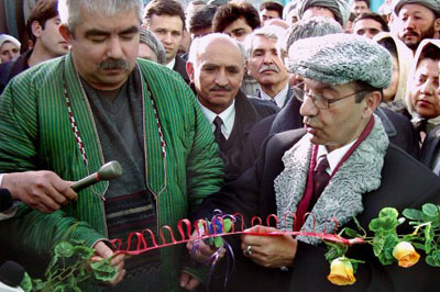 Information and Culture Minister Sayed Makhdoom Raheen (R) cuts the ribbon at the opening of a new non-government television station, Aina TV, in northern Afghan province of Jawzjan