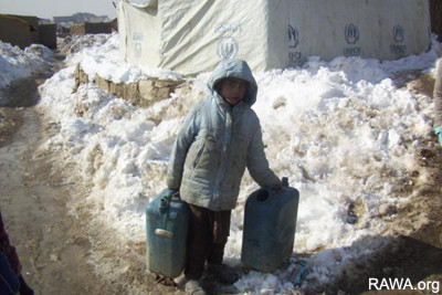 A child carrying water in the Helmandi IDP Camp in the outskirts of Kabul