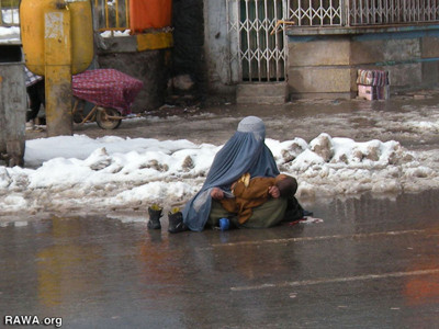 A woman sits on a wet road with her child in her lap