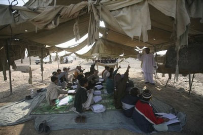Returned Afghan refugee boys study at a makeshift school