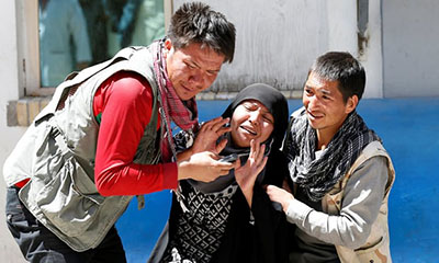 Relatives of victims mourn at a hospital after a suicide attack in Kabul outside a voter registration centre