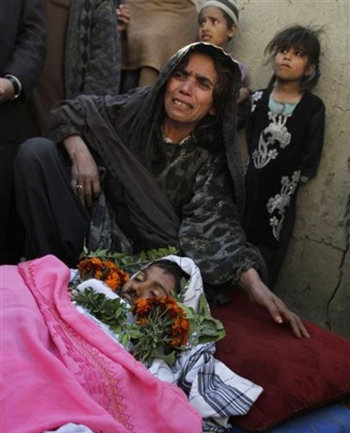 An Afghan woman mourns over the body of her son