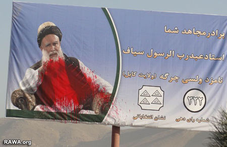 A poster of Sayyaf in Kabul which has been attacked by red color