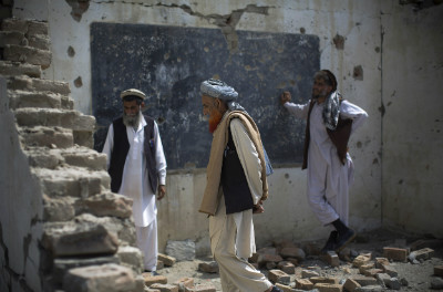 Afghan men walk through the debris of their destroyed school in a village in Nangarhar province Afghanistan